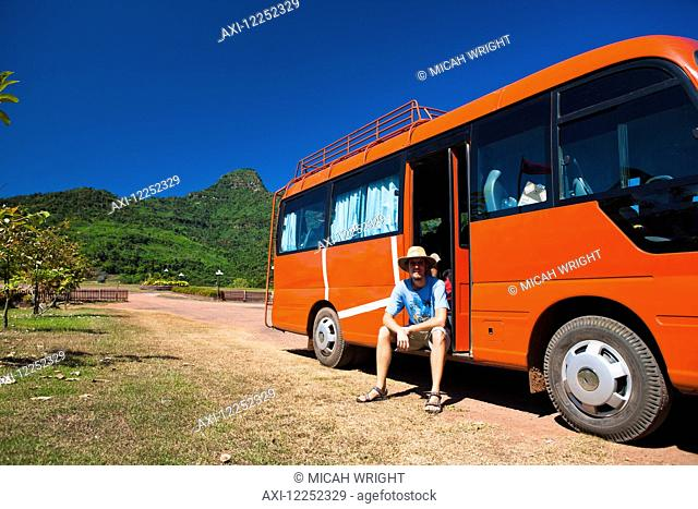 A man sits and waits in a tour bus after a temple tour; Wat Phu, Loas