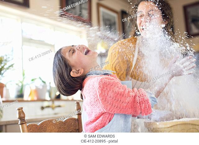 Mother and daughter playing with flour in the kitchen