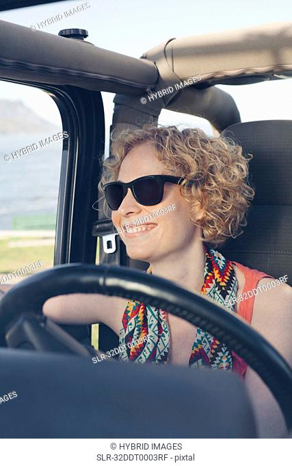 Smiling woman driving jeep