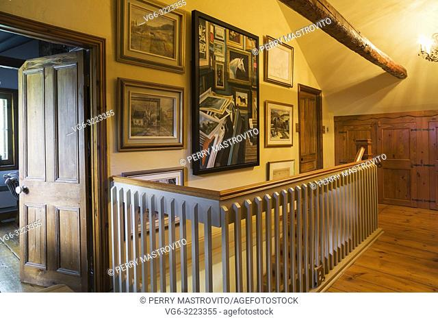 Opened guest bedroom pinewood door and railings surrounding the staircase on the hallway on the upper floor inside an old circa 1850 Canadiana cottage style...