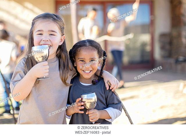 Portrait of two happy girls drinking from goblets