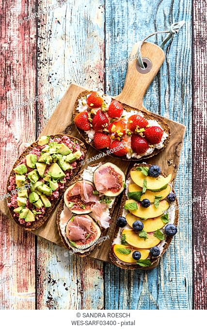 Various sandwiches, strawberry, fig, nectarine, avocado, on chopping board