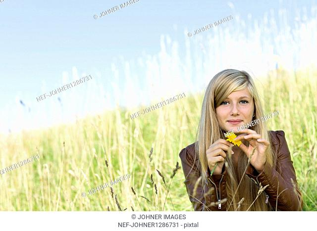 Portrait of girl holding marigold in field