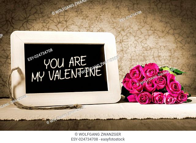 Image of a slate blackboard with message YOU ARE MY VALENTINE in sepia color and pink roses