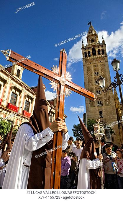Penitents and Giralda.Calle Argote de Molina. Holy Week procession `El Carmen Doloroso' Holy Wednesday Seville Spain