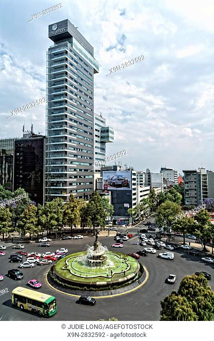 Mexico City, Mexico. Overlooking a Traffic Circle On Paseo de la Reforma, Puente de la Diana Cazodora Monument in the Center. Traffic Going By