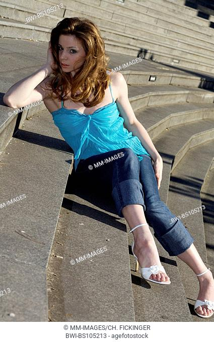 young woman sitting on a staircase, Germany