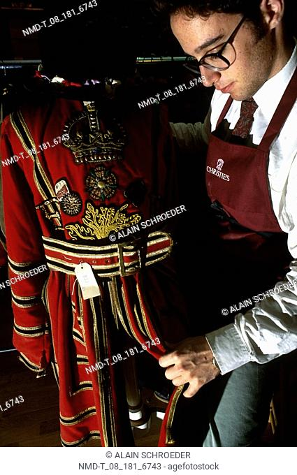 Close-up of a fashion designer checking a dress, Christie's Beefeater's Dress, London, England