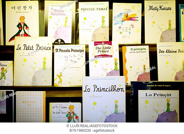 Shelves in a book shop with the book The Little Prince in different editions and languages