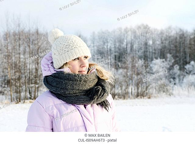 Mid adult woman wearing winter clothing in snow covered field