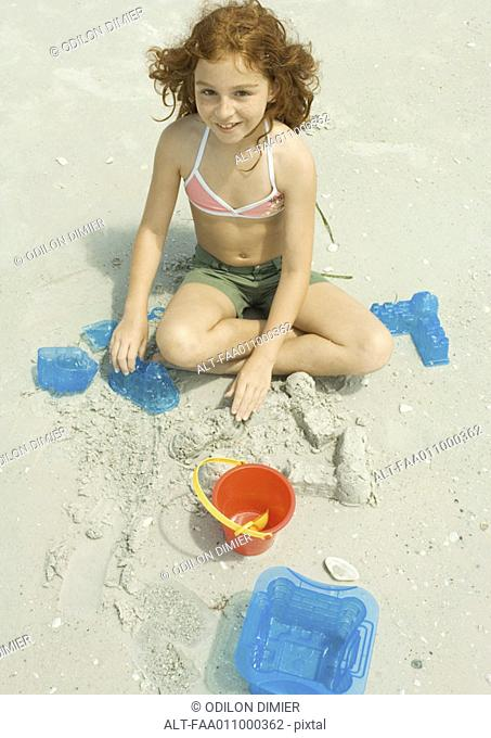 Girl playing in sand on beach