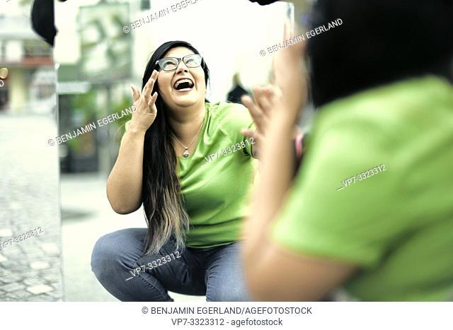 happy woman seeing herself in mirror at street, in Paris, France