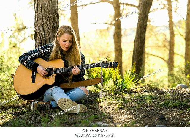 Young woman playing guitar in nature
