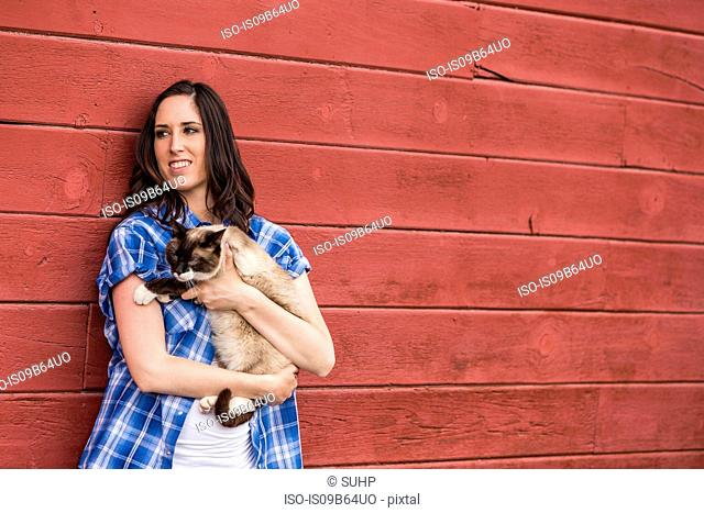 Portrait of young woman holding cat, smiling