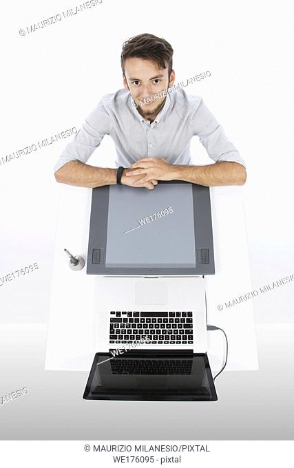 Graphic designer seen from above with tablet and laptop, he is smiling and with his arms resting at the desk