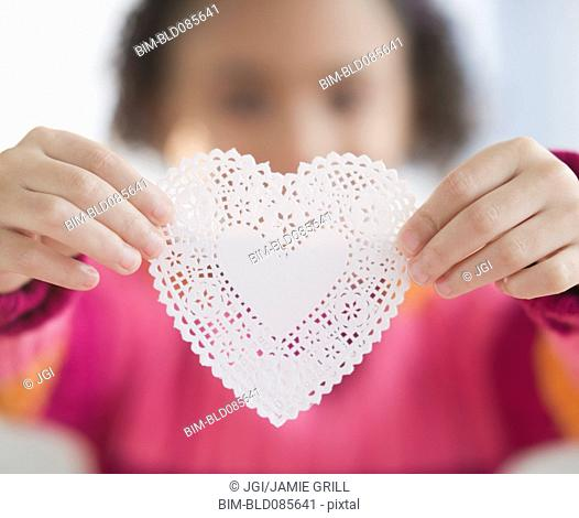 African American girl holding heart-shaped doily
