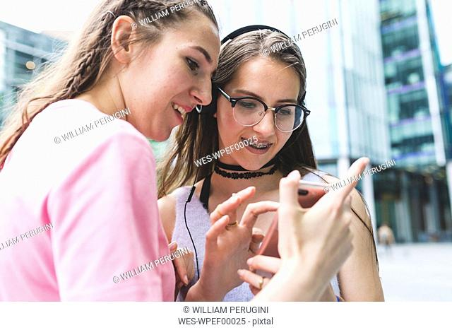 Two happy teenage girls sharing cell phone in the city