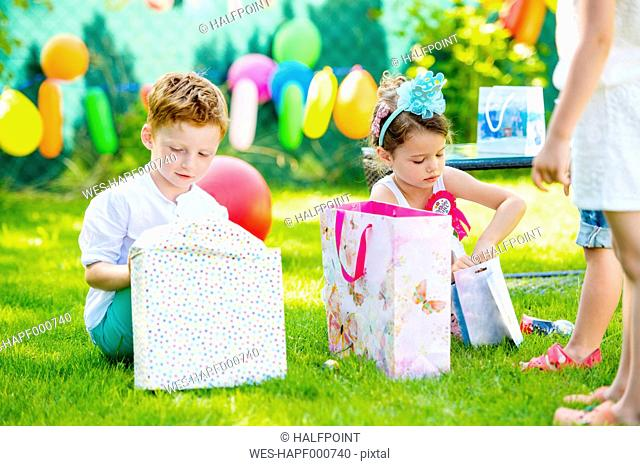 Little boy and girl unpacking birthday presents in the garden