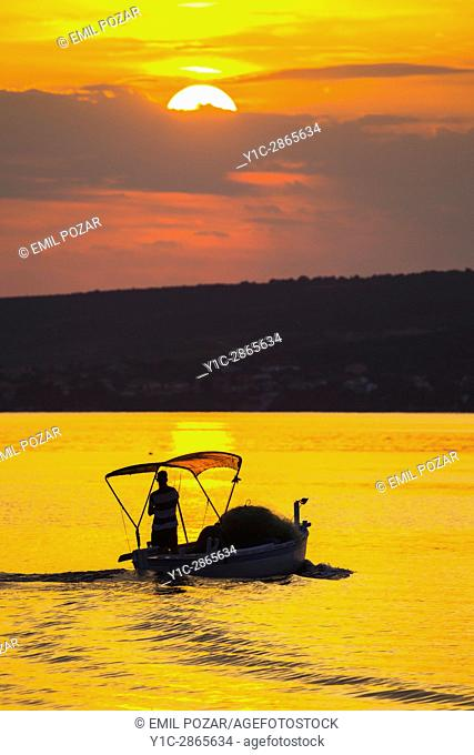 Sunset setting sun lonely boat Novigrad small coastal town in Croatia
