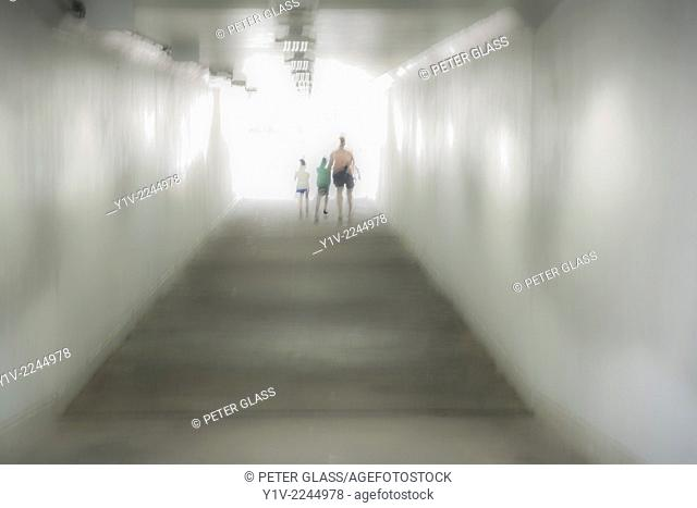 Mother and children walking through an underground tunnel