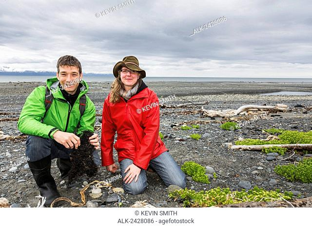 Couple kneeling on sandy Bishop's Beach, Kachemak Bay, Homer, Southcentral Alaska, USA