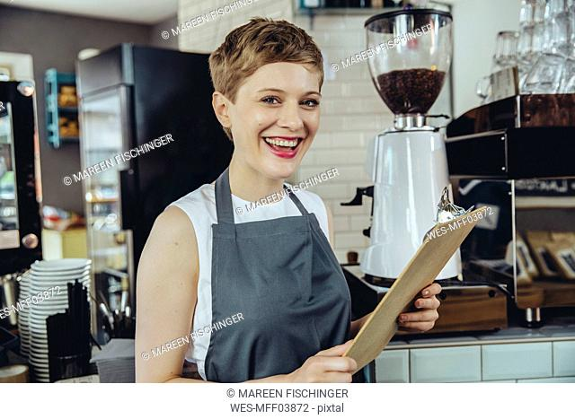 Portrait of laughing waitress holding menu in a cafe