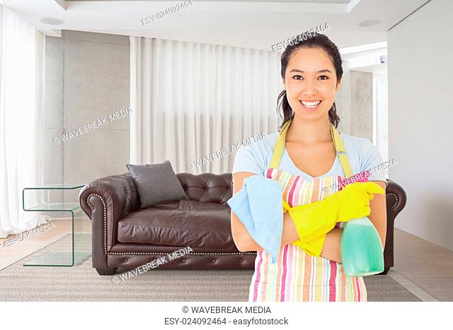 Composite image of woman standing with arms crossed holding cleaning products