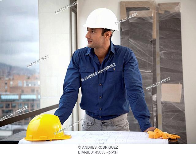 Hispanic man in hard-hat on construction site
