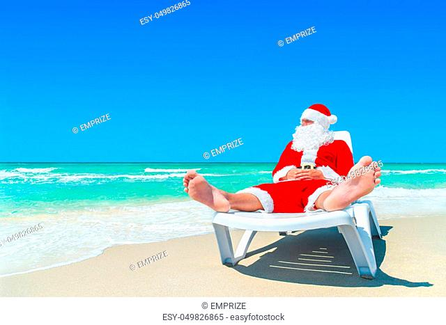 Santa Claus relax on sunlounger at ocean tropical sandy beach. Me? ry Christmas and Happy New Year travel destinations concept