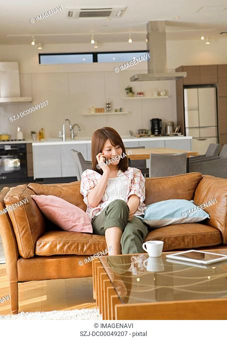 Middle-aged woman leaning against a sofa and talking on a phone