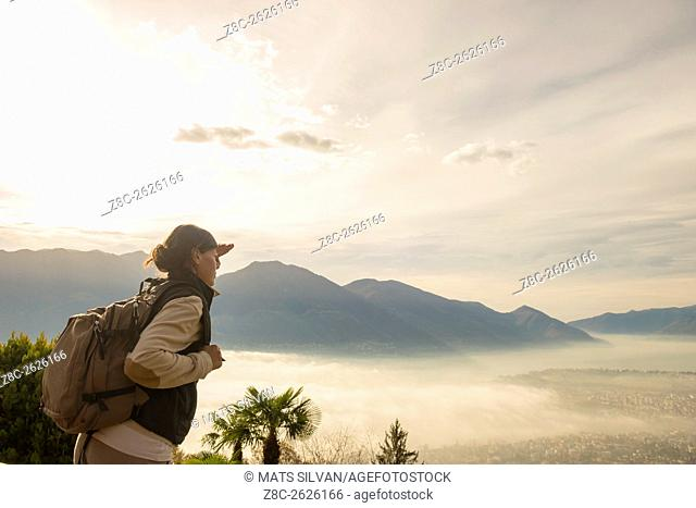 Woman with raised hand and backpack enjoy panoramic view with sea of fog over alpine lake Maggiore with mountain in Ticino, Switzerland