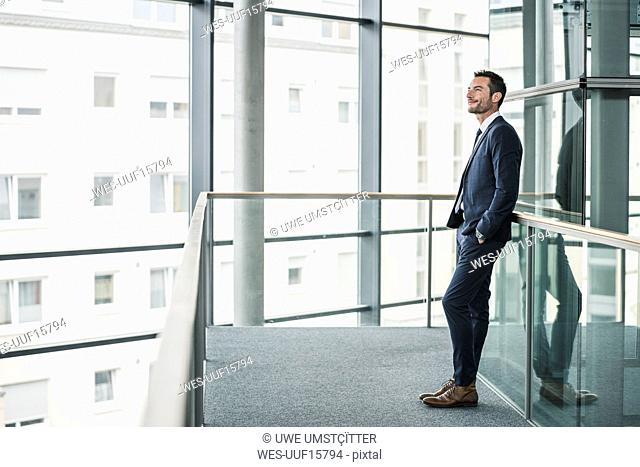 Successful businessman standing in office building, looking out of window, daydreaming