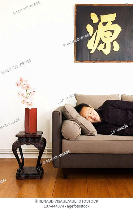 Man taking nap in apartment with Asian decor. Paris. France