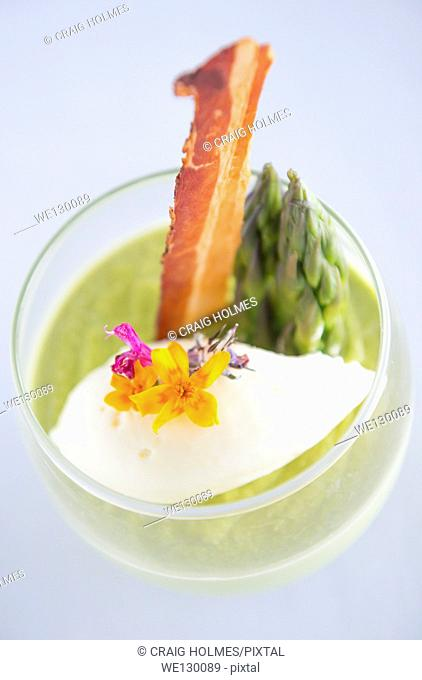 Asparagus soup served in a glass, decorated with bacon, asparagus tips and flowers