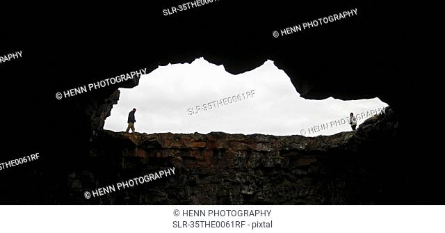 People walking around mouth of cave