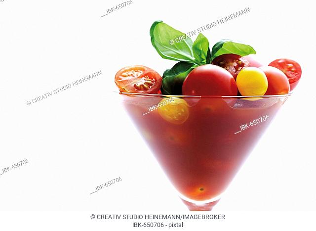 Red and yellow grape tomatoes with tomato juice and basil
