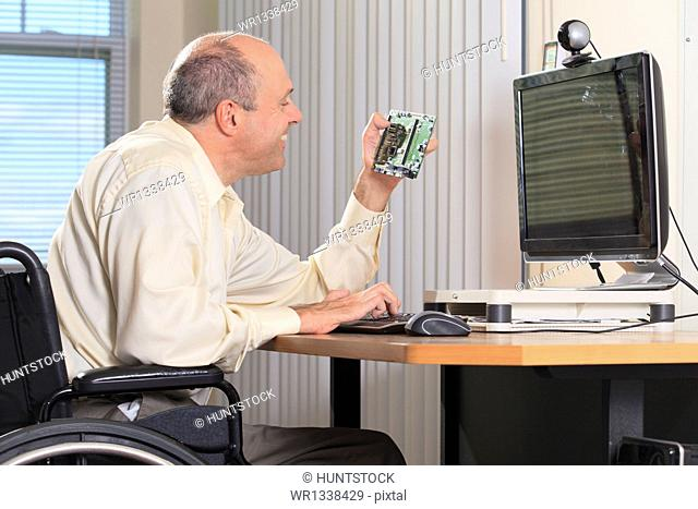 Man with Friedreich's Ataxia and deformed hands as an electronic design engineer at his workstation with a circuit board