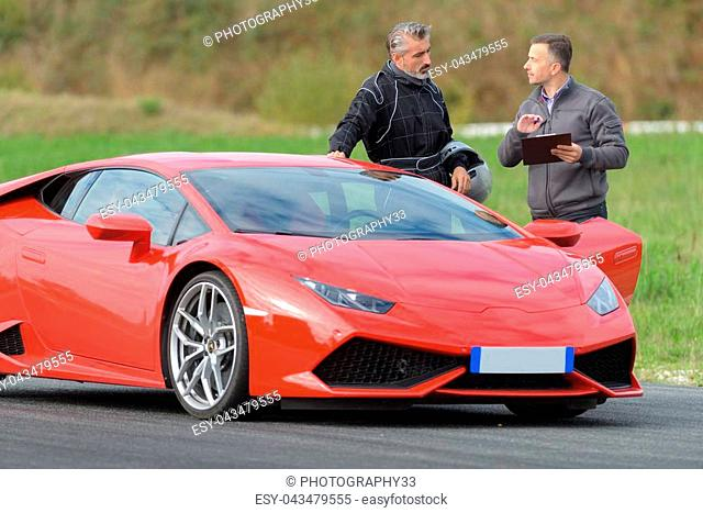 Man stood by sports car on circuit