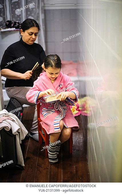 Mother brushing her daughter's hair after the shower