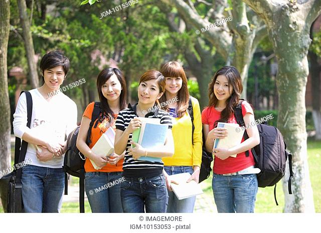 Five college students holding books and standing with schoolbags in the campus, Studying, Education