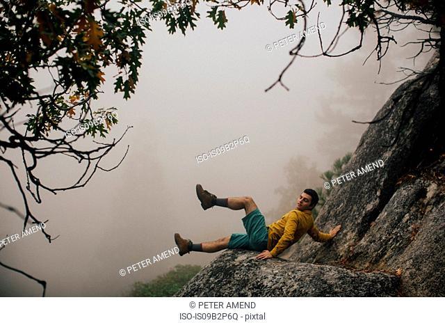 Young man falling on rock, near Shaver Lake, California, USA
