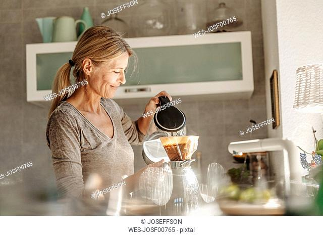 Woman at home in kitchen preparing coffee