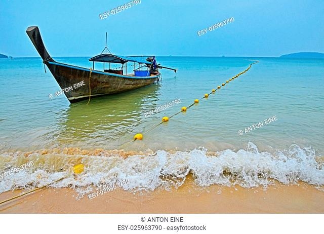 Traditional Thailand old vintage unpainted long tail boat without engine in transparent turquoise water crossed with yellow float buoys