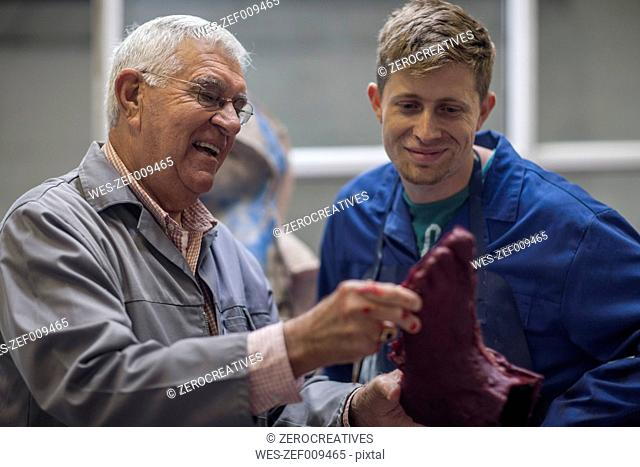 Instructor showing trainee cast in workshop