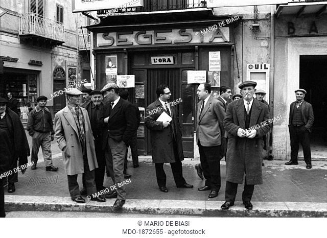 Some men discussing at the entrance of the former Garage Segesta, where a public debate about Franca Viola's case was held by Epoca