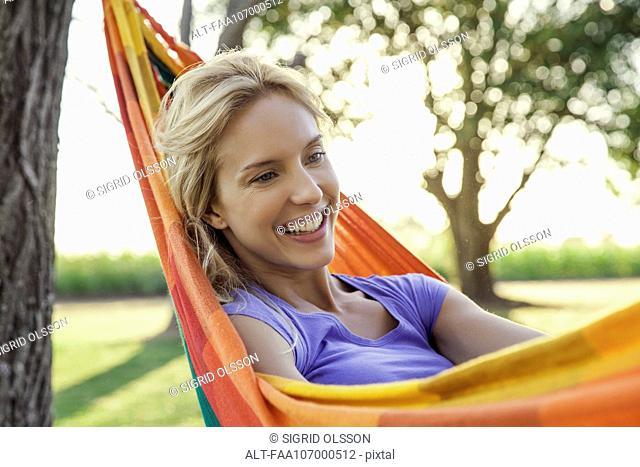 Woman relaxing in hammock, portrait
