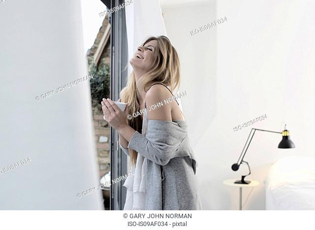Young woman standing at window holding hot drink
