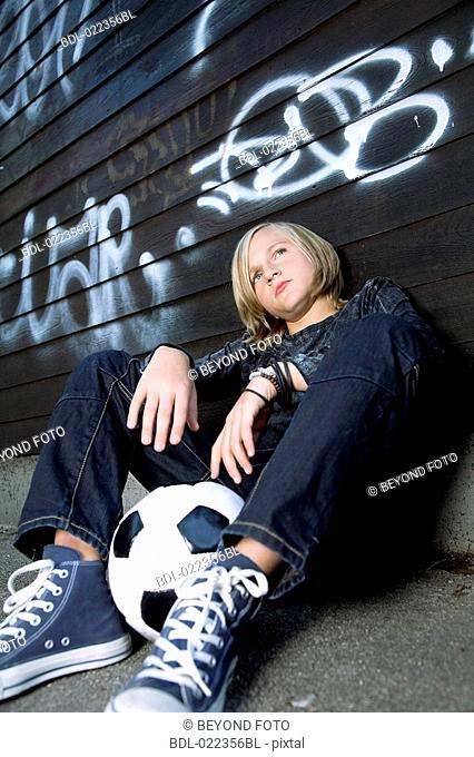portrait of sulking blond boy with football