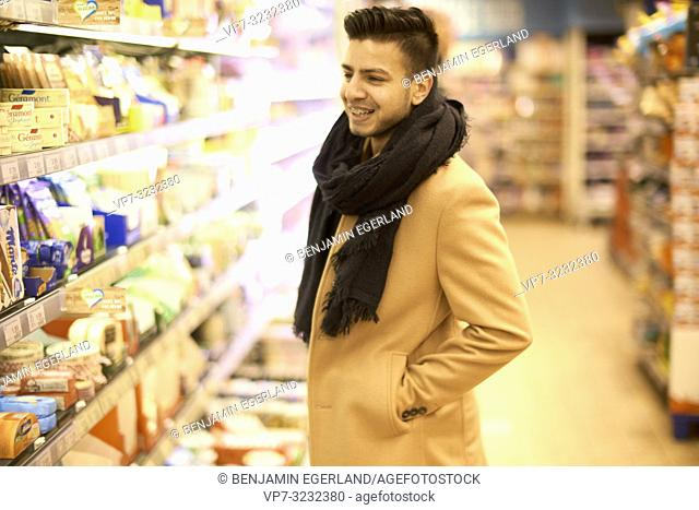 young happy man next to cooling shelf in supermarket, in Munich, Germany