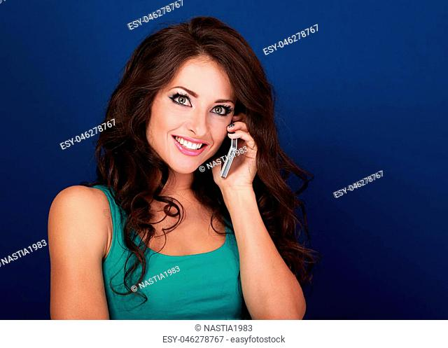 Emotional excited young woman talking on mobile phone on blue background